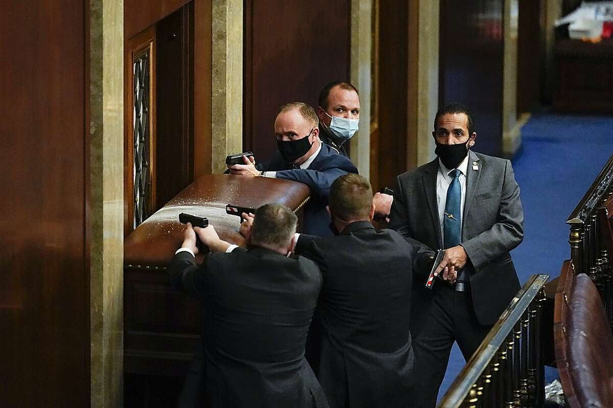 Capitol officers point guns at a barricaded door as rioters try to breach the House chamber on Jan. 6.
