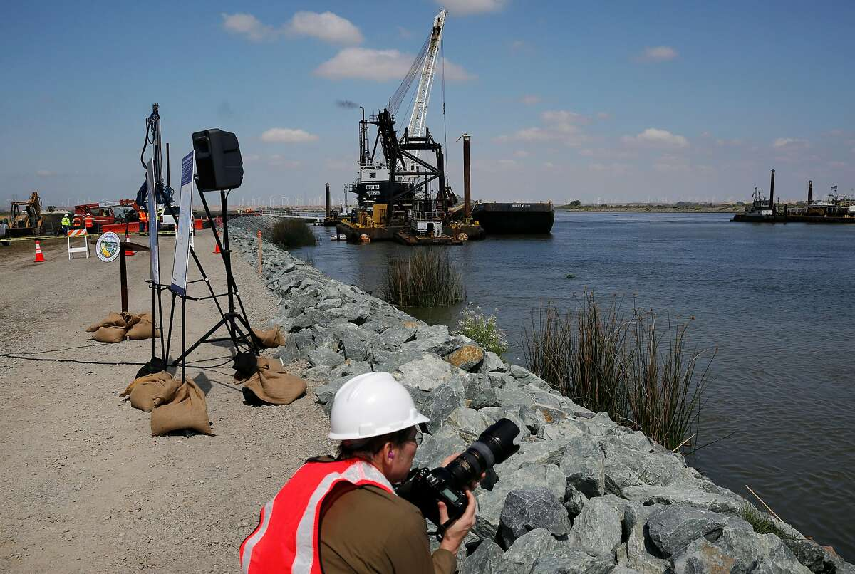 Bill Kelley III shoots photographs for the state Department of Water Resources of the saltwater barrier construction in the delta in 2015. A similar rock wall is to be constructed in the same location starting next month.