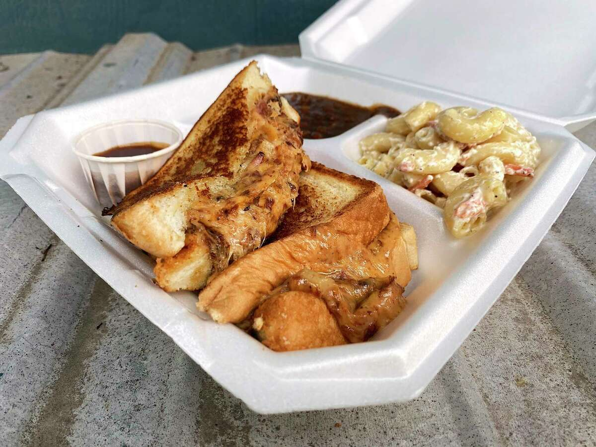 A grilled cheese sandwich is made with shredded pork rib meat and cheese on Texas toast with barbecue sauce and sides such as barbecue baked beans and macaroni salad at Bar B Que Done Wright, a food truck on the Southwest Side doing American barbecue with Philippine influences.