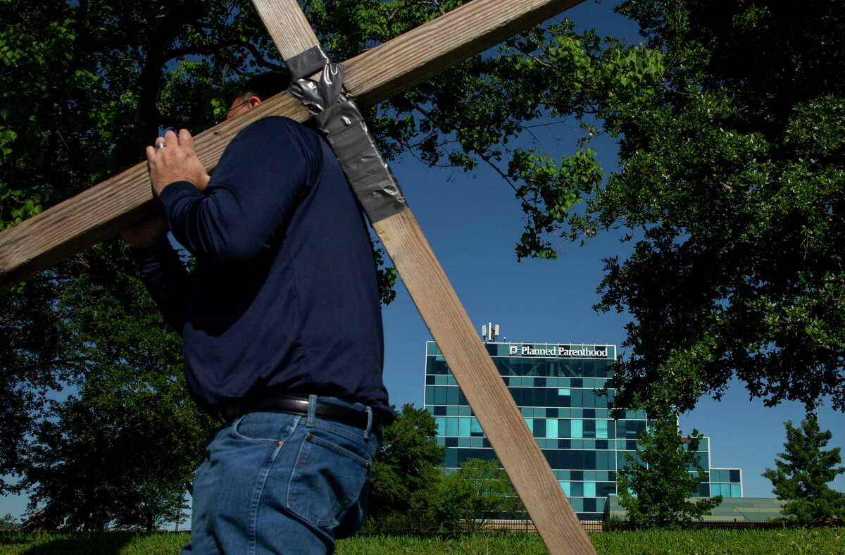 A man carries a cross during the 12 stations of the cross, which people used to protest abortion outside the Planned Parenthood building at 4600 Gulf Freeway Friday, April 19, 2019, in Houston.