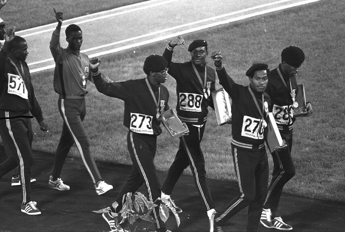 Three out of four members of the United States 4x400-meter relay team, right, hold up clenched fists as they leave the Olympic stadium after receiving their gold medals during the Mexico City Games. The four, from left, are Ron Freeman , Vince Matthews, Lee Evans (270) and Larry James.