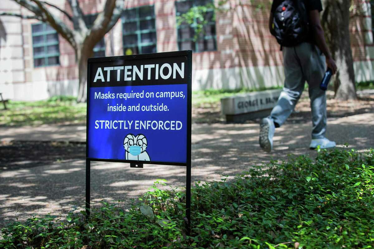 A Rice University student walks by sign advising people about the university's mask policy, Monday, April 26, 2021, in Houston. An email from the university administration was released and said that masks will no longer be required outdoors as long as people socially distance at least 3 feet and that those who are fully vaccinated can opt out of weekly testing.