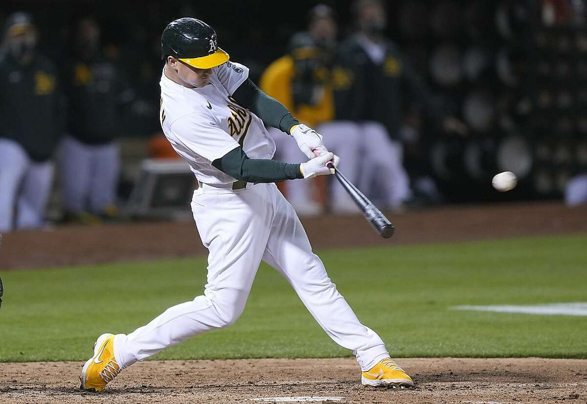 OAKLAND, CALIFORNIA - MAY 18: Matt Chapman #26 of the Oakland Athletics hits an RBI double scoring Ramon Laureano #22 against the Houston Astros in the eighth inning at RingCentral Coliseum on May 18, 2021 in Oakland, California. (Photo by Thearon W. Henderson/Getty Images)