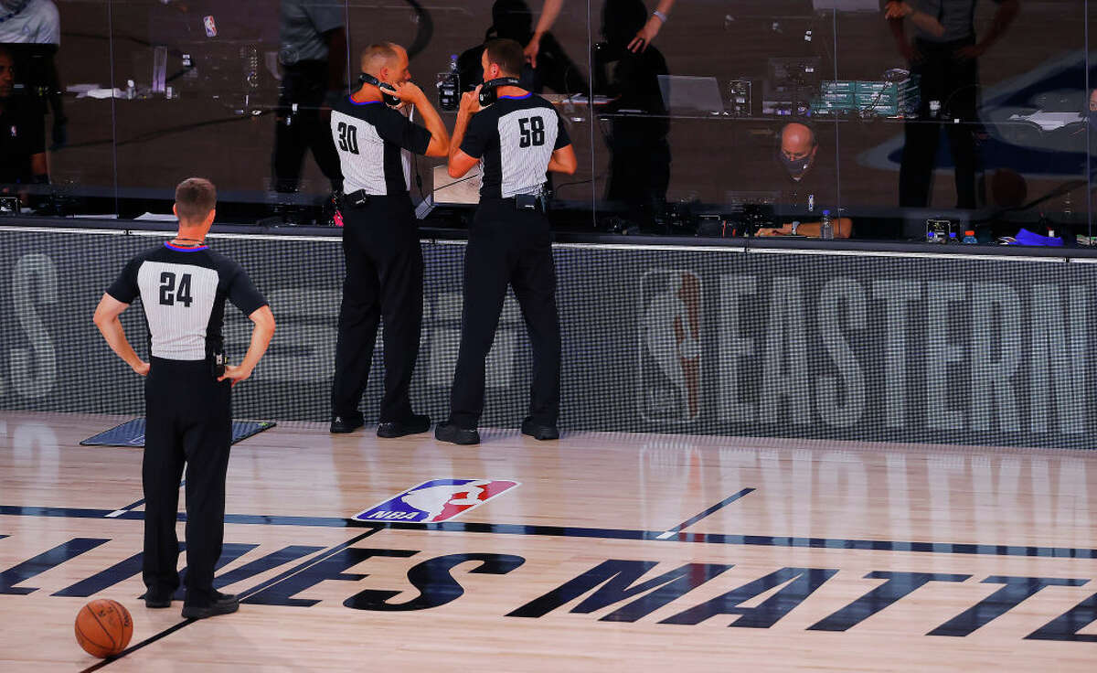 Referee John Goble #30, referee Josh Tiven #58 and referee Kevin Scott #24 discuss a call during the fourth quarter in Game Five of the Eastern Conference Finals during the 2020 NBA Playoffs.