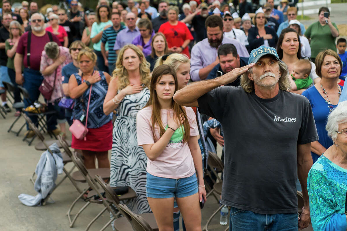 Richard Seamster of Midland holds a salute while listening to the national anthem during a dedication ceremony for the Sanford Veterans Monument and First Responders Monument Wednesday, May 19, 2021 in downtown Sanford. The occasion marked the beginning of the Sanford Rising celebration in honor of the one-year anniversary of the May 2020 dam failures and flood. (Katy Kildee/kkildee@mdn.net)