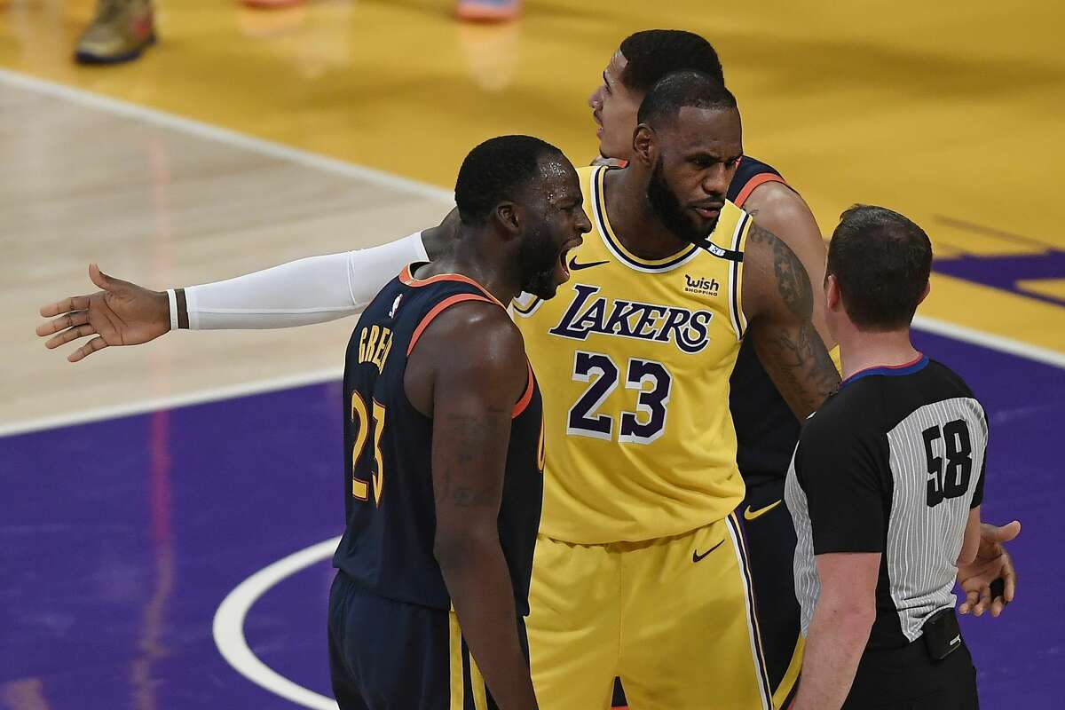 Draymond Green #23 of the Golden State Warriors and LeBron James #23 of the Los Angeles Lakers argue with referee Josh Tiven #58 during the first half of an NBA Tournament Play-In game at Staples Center on May 19, 2021 in Los Angeles, California.