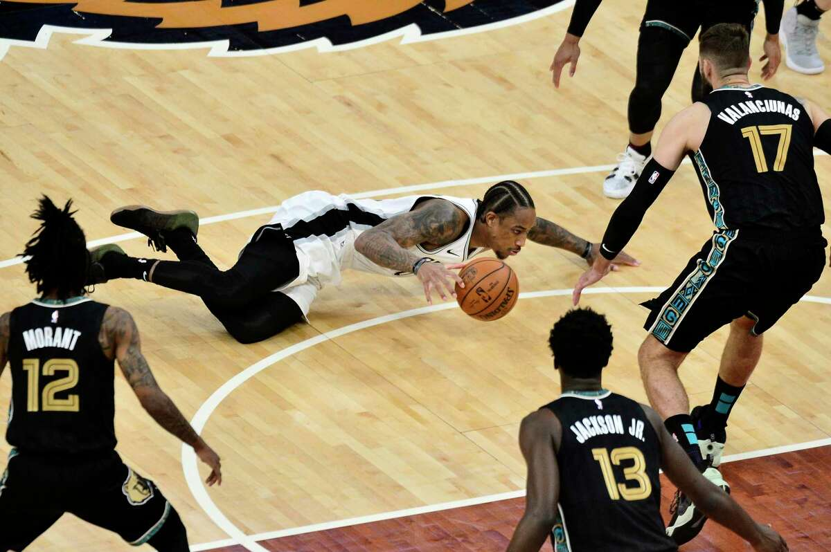 Spurs forward DeMar DeRozan falls to the court during the first half of the team's NBA Western Conference play-in game against the Grizzlies on Wednesday, May 19, 2021, in Memphis, Tenn.