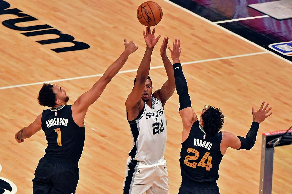 Rudy Gay (22) of the Spurs shoots against Kyle Anderson (1) and Dillon Brooks (24) of the Grizzlies during the first half of the play-in tournament game at FedExForum on May 19, 2021 in Memphis, Tenn.