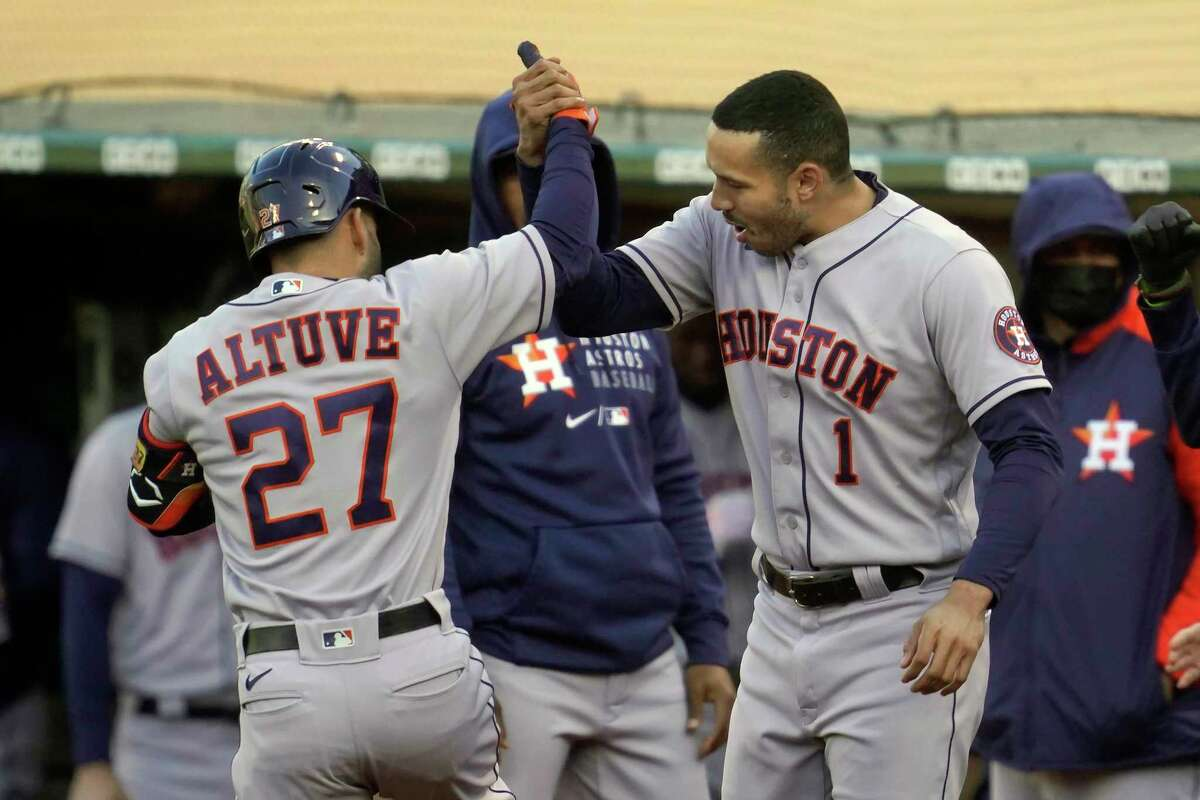 Houston Astros' Jose Altuve (27) is congratulated by Carlos Correa (1) after hitting a home run against the Oakland Athletics during the first inning of a baseball game in Oakland, Calif., Wednesday, May 19, 2021. (AP Photo/Jeff Chiu)