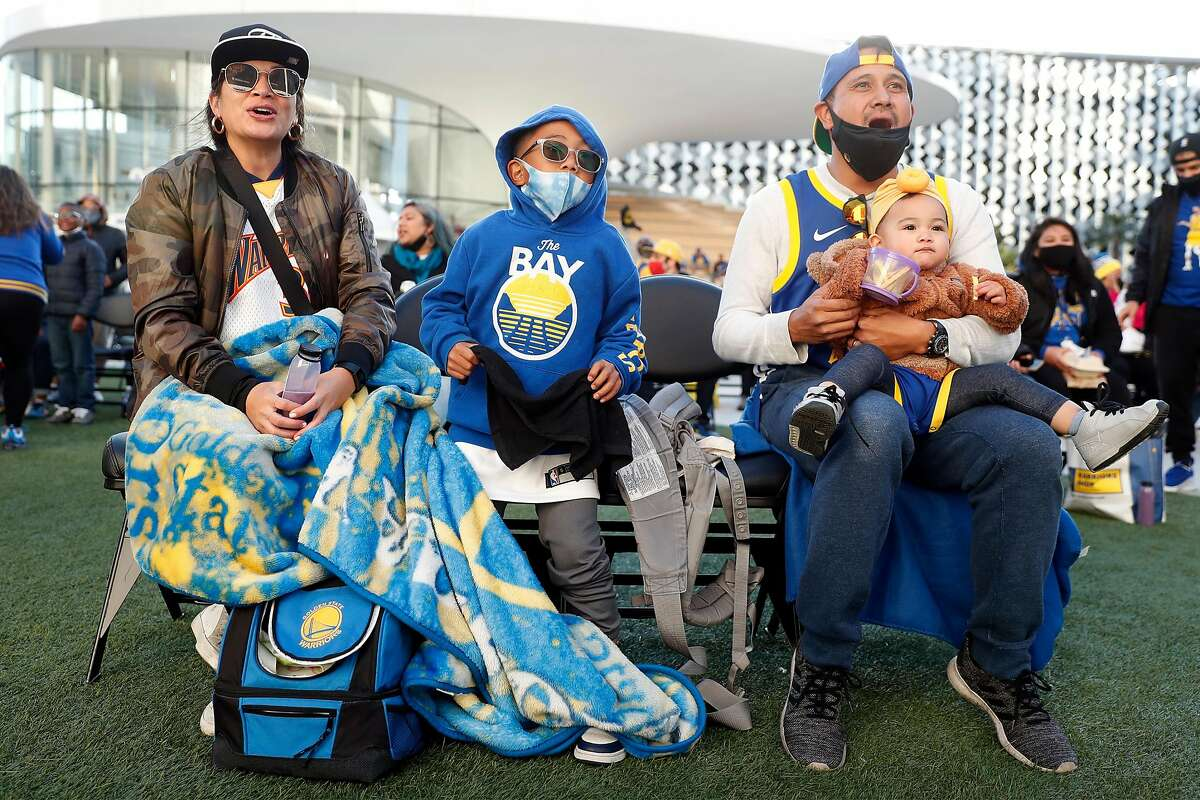 Golden State Warriors fan Lattimer Luis of Antioch holds his 18-month-old daughter, Pia, alongside his wife, Pauline, and son, Shea, 6, during an event at Chase Center in San Francisco.