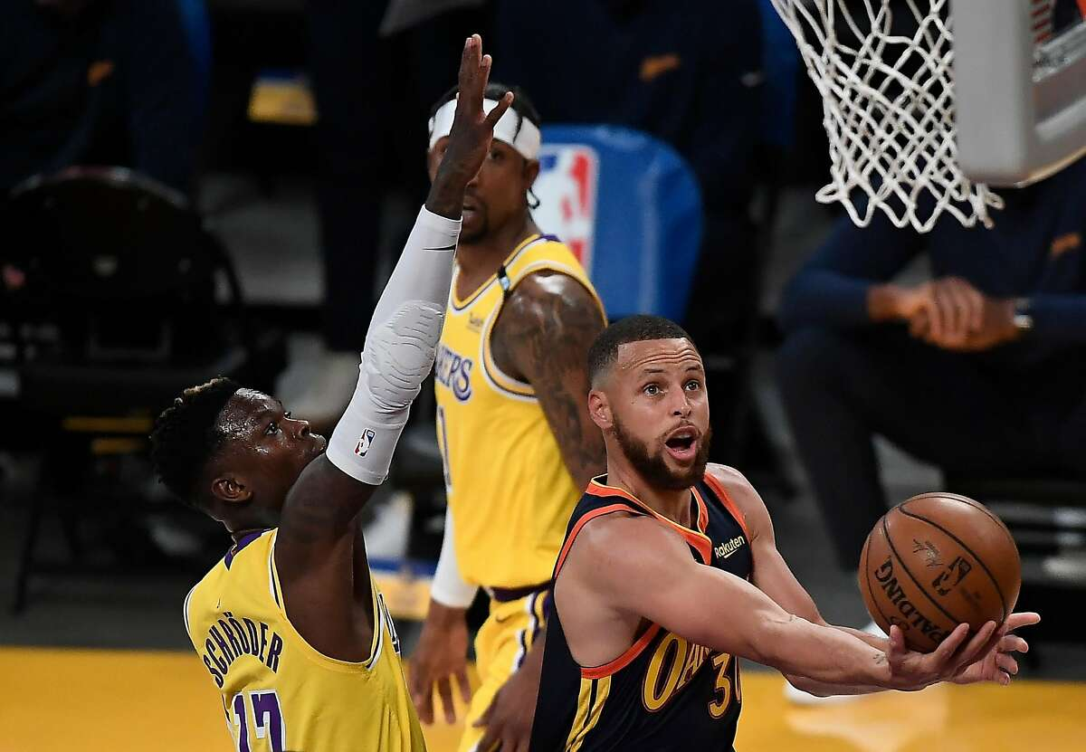 Stephen Curry drives to the basket as Lakers guard Dennis Schroder defends during the first half Wednesday night.