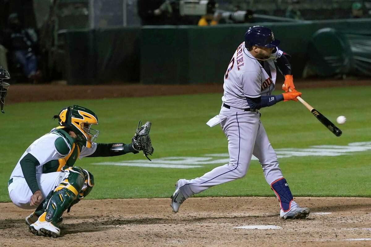 Houston Astros' Yuli Gurriel, right, hits a two-run double in front of Oakland Athletics catcher Aramis Garcia during the eighth inning of a baseball game in Oakland, Calif., Wednesday, May 19, 2021. (AP Photo/Jeff Chiu)