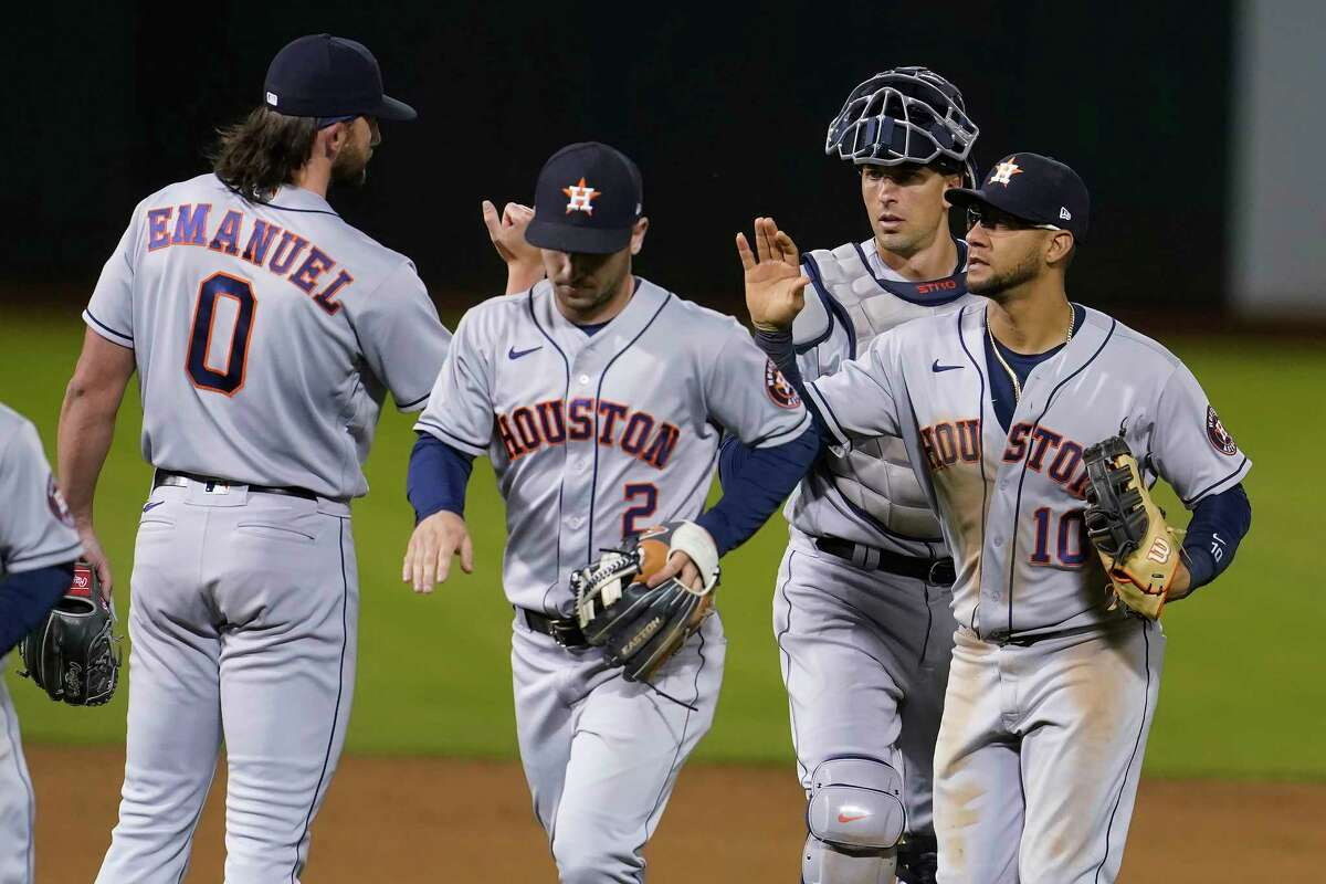Houston Astros' Kent Emanuel, from left, celebrates with Alex Bregman, Jason Castro and Yuli Gurriel after the Astros defeated the Oakland Athletics 8-1 in a baseball game in Oakland, Calif., Wednesday, May 19, 2021. (AP Photo/Jeff Chiu)