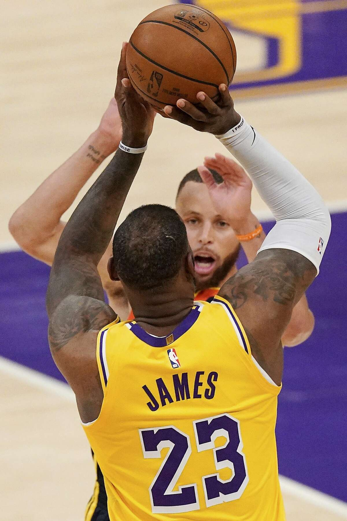 Los Angeles Lakers forward LeBron James, below, shoots and makes a three-point shot as Golden State Warriors guard Stephen Curry defends with one minute left in an NBA basketball Western Conference Play-In game Wednesday, May 19, 2021, in Los Angeles. (AP Photo/Mark J. Terrill)