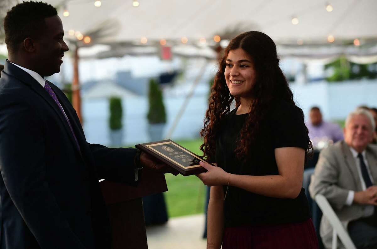 P-Tech high school students including Zainab Khan, above, and Alex Zelman, left, celebrate their graduation whikle receiving a plaque from IBM Program Manager Robert Hutchinson during a reception Wednesday at Longshore Pavillion in Norwalk. Students in the technical program earn their associates degree while also earning their high school diploma. For photos from the NCC comencement ceremony, see A16