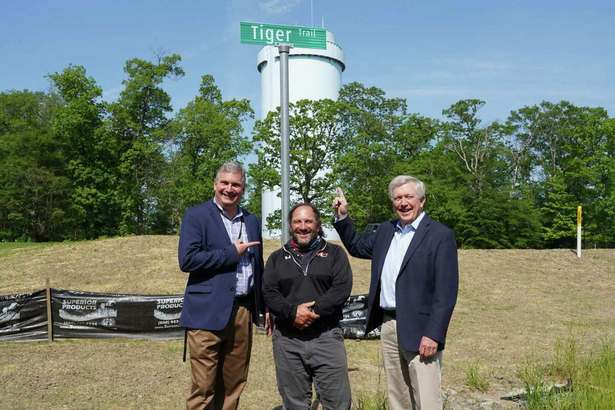 Superintendent Bryan Luizzi stands to the left of DPW head Tiger Mann and First Selectman Kevin Moynihan soon after they surprised Mann with the sign for the trail between New Canaan High School and Waveny Park on Thursday, May 20.