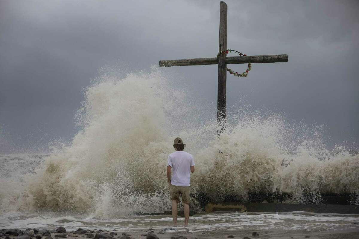 Hunter Clark watches waves crash ashore as outer bands from Hurricane Laura begin to hit the coast Wednesday, Aug. 26, 2020, in High Island. Clark is from Bogata, Texas, near Paris, Texas, and they came to board up windows at a beach house in High Island.