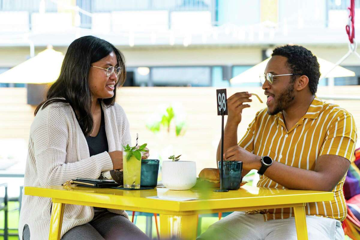 Denise Tobilla and Khalyl Smith talk as they eat and have a drink, Thursday, May 13, 2021, at the bar Space Cowboy in Houston. The CDC relaxed their mask guidelines for vaccinated people on Thursday. Both are vaccinated, and said they are still wearing masks out of precaution for others. Tobilla, who was at a bar for the first time since the pandemic started, said she plans to keep wearing a mask until herd immunity is reached.