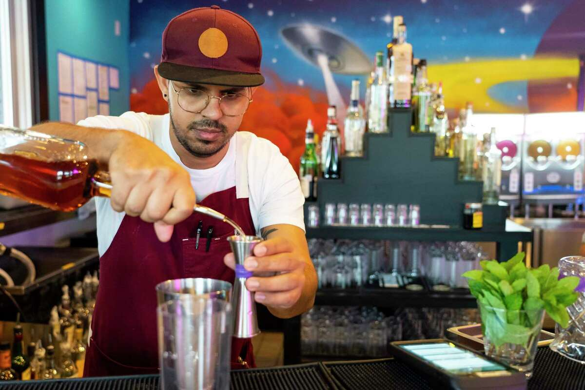 Bartended Javi Alburjas pours a drink, Thursday, May 13, 2021, at the bar Space Cowboy in Houston. The CDC officially relaxed their mask guidelines for vaccinated people on Thursday.
