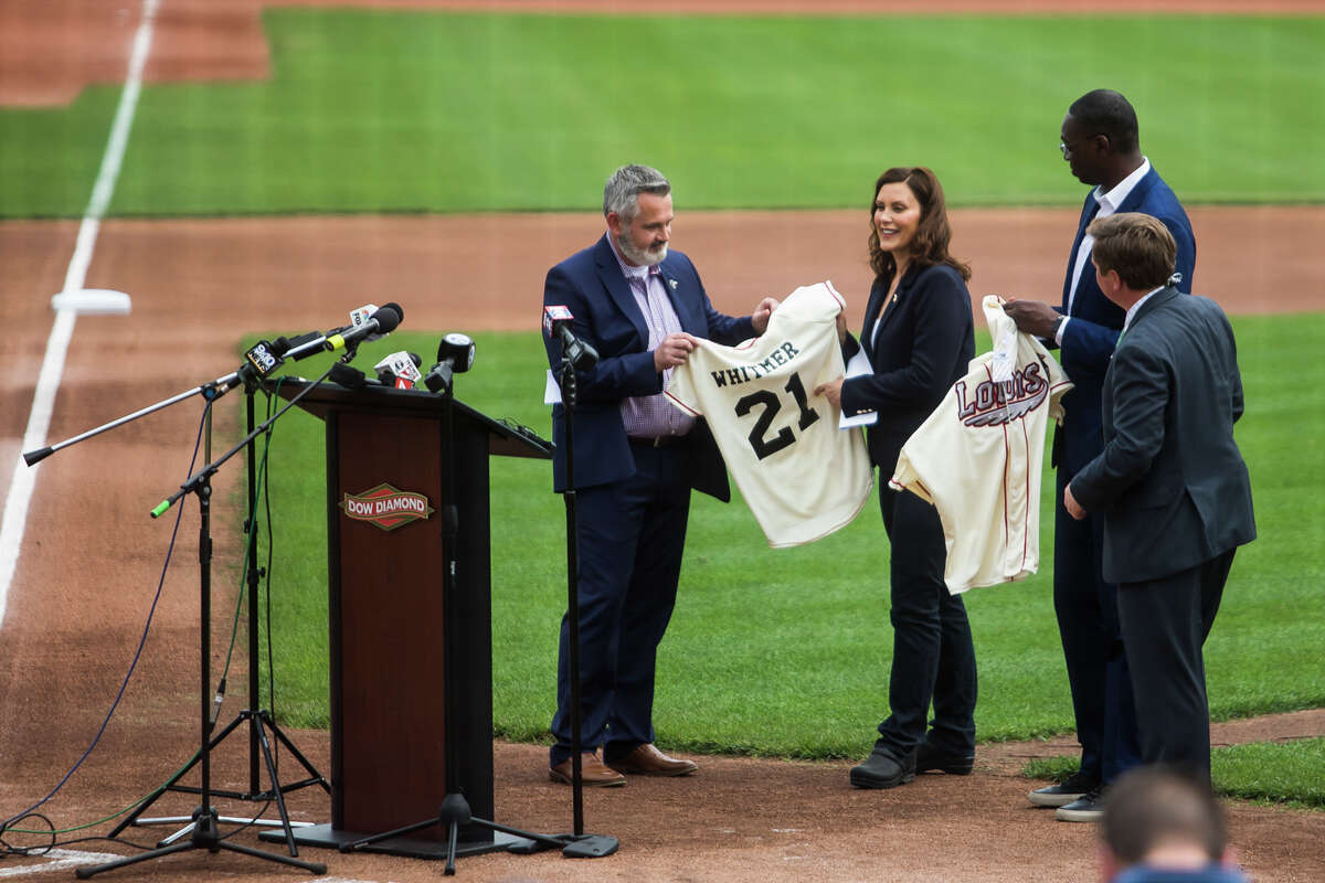 Great Lakes Loons President Chris Mundhenk, left, presents Great Lakes Loons jerseys to Gov. Gretchen Whitmer and Lt. Gov. Garlin Gilchrist during a press conference Thursday, May 20, 2021 at Dow Diamond in Midland, where Whitmer announced all outdoor capacity limits will be lifted across the state after June 1. Whitmer was also joined by Midland Mayor Maureen Donker, Dow CEO Jim Fitterling and Great Lakes Bay Regional Alliance President Matthew Felan. (Katy Kildee/kkildee@mdn.net)