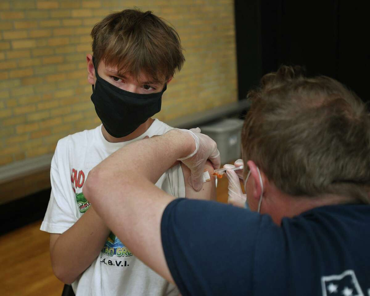 Kaden Kohler, 15, of Milford, receives his first dose of the Pfizer Covid-19 vaccine at a Yale New Haven Health vaccination clinic at the Parsons Complex gymnasium in Milford on May 17.