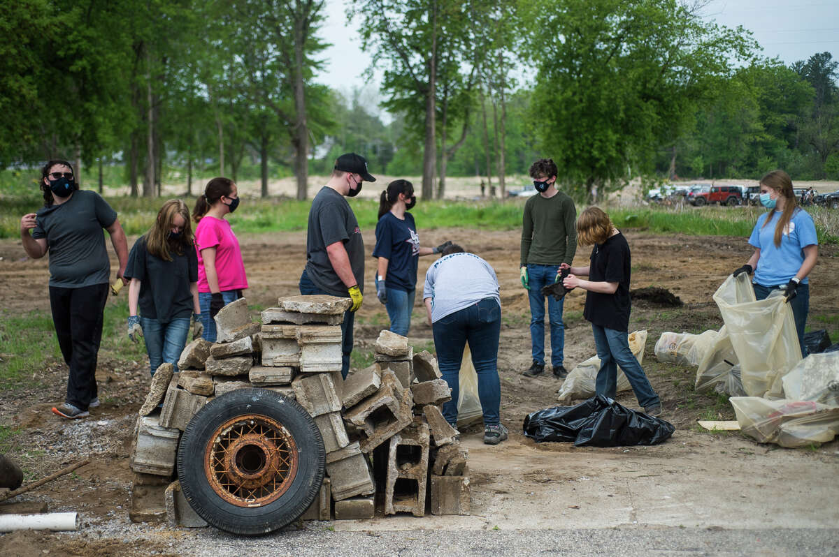 Meridian Early College High School students work to clear debris from Porte Park as part of the Sanford Rising celebration in honor of the one-year anniversary of the May 2020 dam failures and flooding, on Thursday, May 20, 2021 in downtown Sanford. (Katy Kildee/kkildee@mdn.net)