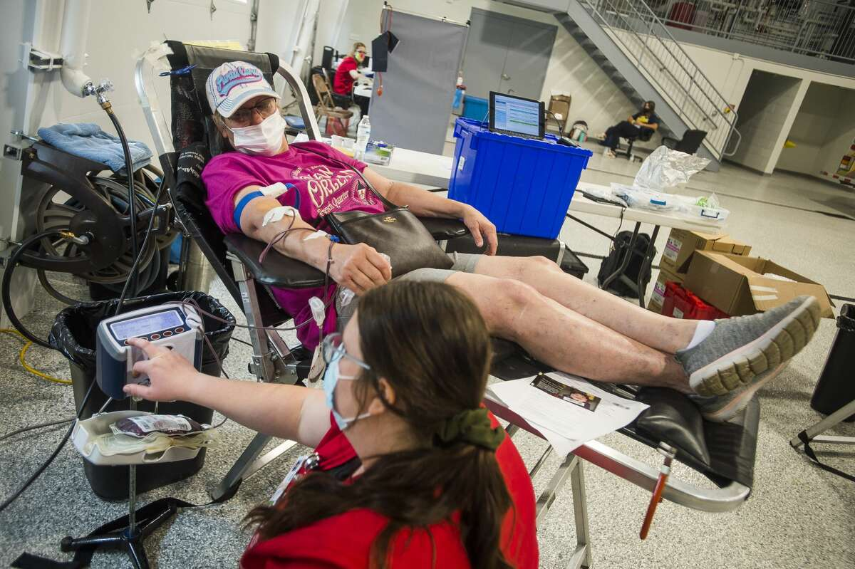 Maddie Mendyk, bottom, assists Jill Carroll of Sanford as she donates blood during a Versiti blood drive Thursday, May 20, 2021 at the Jerome Township Fire Station in Sanford. (Katy Kildee/kkildee@mdn.net)