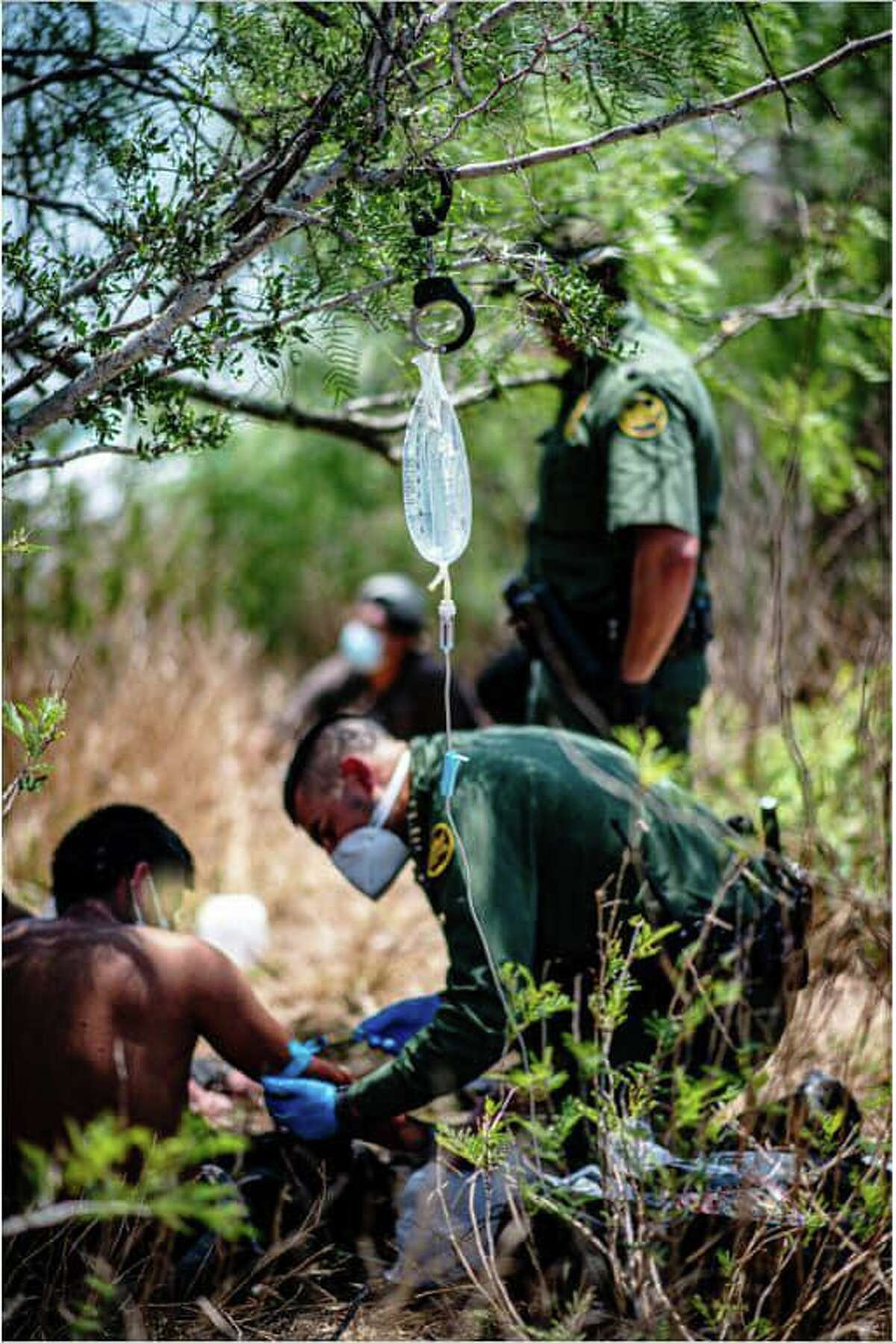 A U.S. Border Patrol agent is seen rendering aid to a migrant who was suffering from severe dehydration.