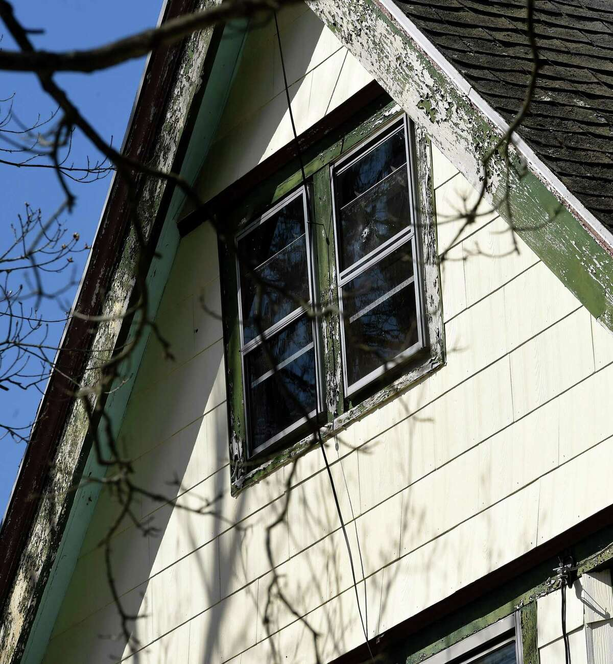 A bullet hole can be seen in the attic window of a house next door to where a shooter fired from a second-floor apartment 241 Main Street in Branford the previous day.