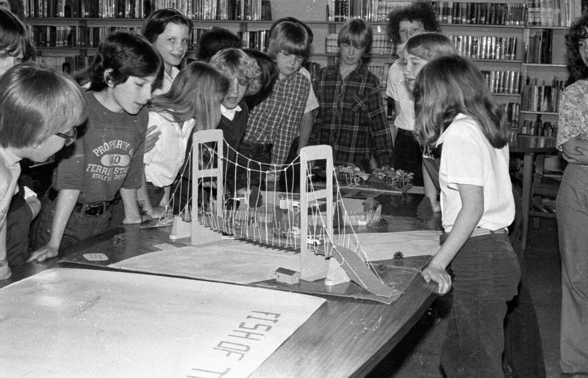 Three Manistee Catholic Centralstudentslook over a model of the Mackinac Bridge built by MCC eighth grade students. Forty-one eighth grader students constructed the project for Michigan Week, which is being held May 16-23. The theme of the exhibit is