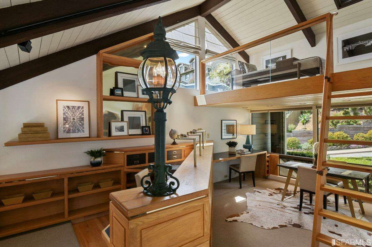 Though much of the home was renovated in the late '80s, this built-in office with loft space above was put in in the '90s. There is a half bath tucked away in the office as well.