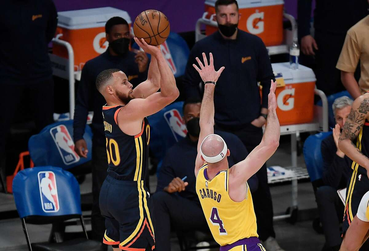 Stephen Curry shoots a 3-pointer as Alex Caruso of the Lakers defends during the final seconds of Wednesday night's first half in Los Angeles. Curry scored 37 points, but the Warriors lost 103-100.