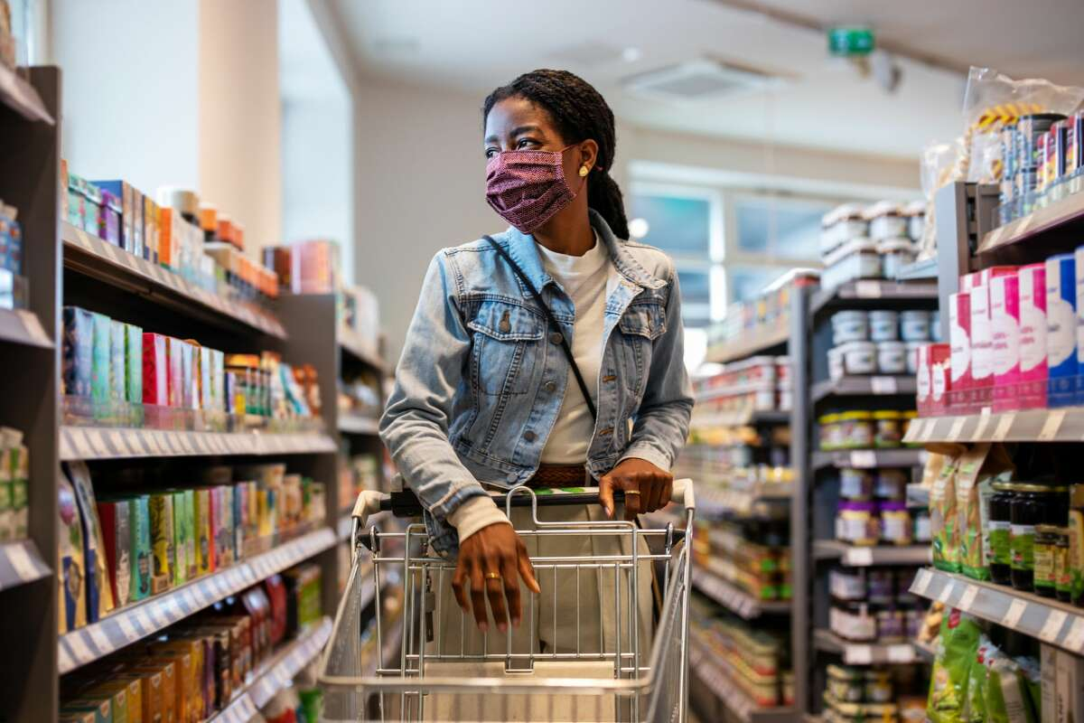 Woman wearing protective face mask buying grocery at a supermarket.