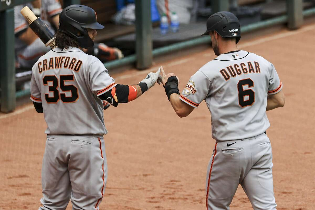 San Francisco Giants' Brandon Crawford, left, celebrates Steven Duggar (6) scoring a run on a passed ball during the fifth inning of a baseball game against the Cincinnati Reds in Cincinnati, Thursday, May 20, 2021. (AP Photo/Aaron Doster)