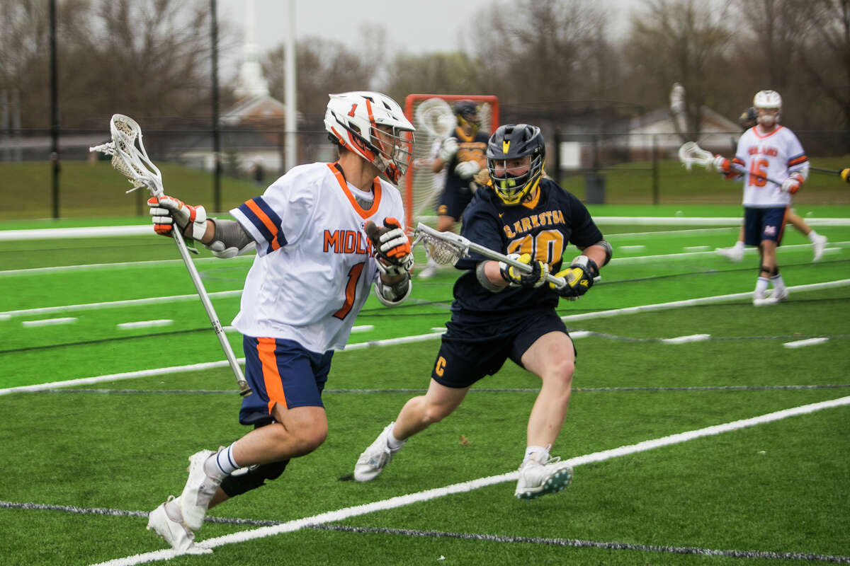 Midland-Dow's Mason Reed advances the ball during an April 9, 2021 match against Clarkston at Dow High's new turf field.