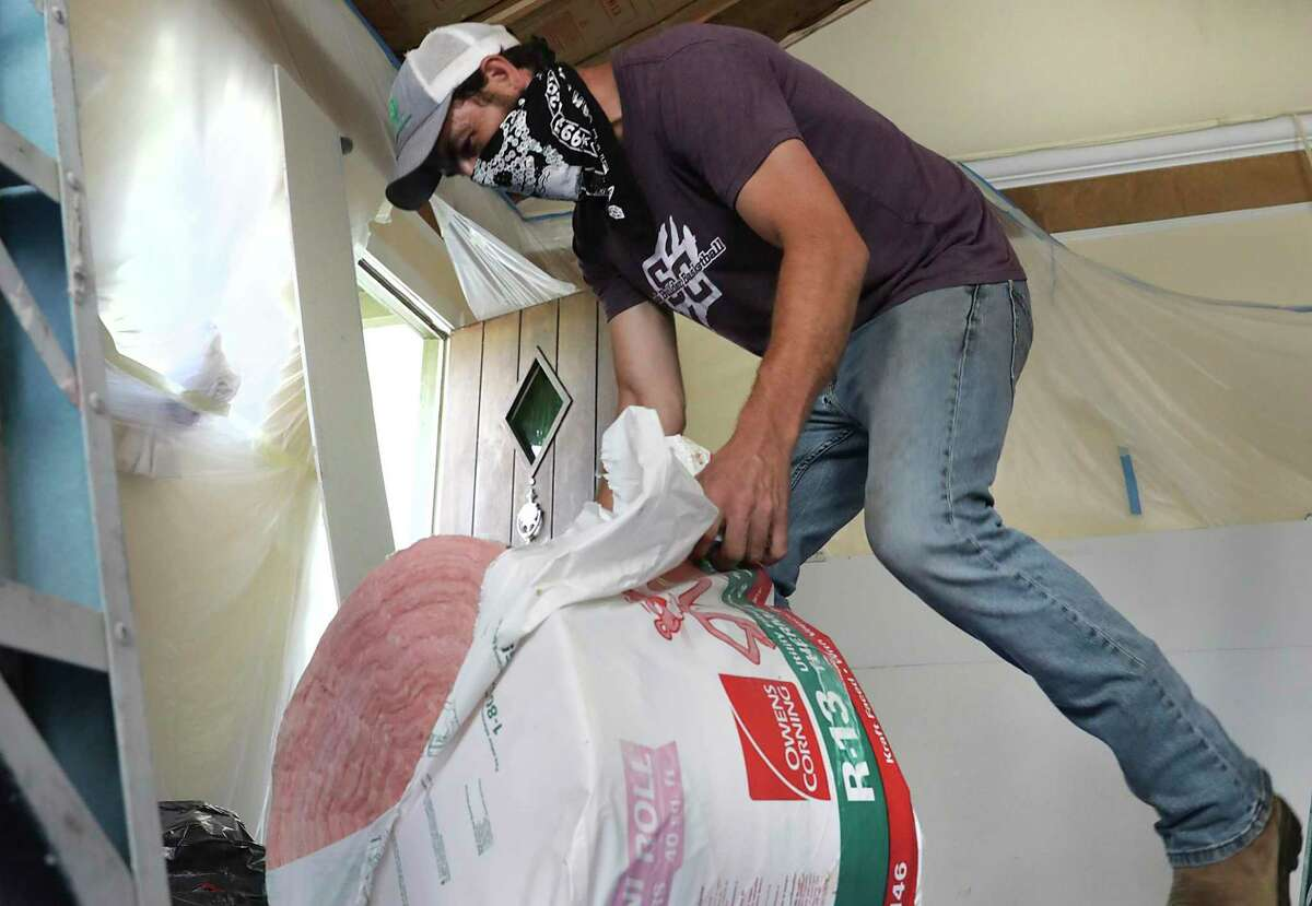 A homeowner opens a roll of insulation to be stapled to the ceiling before the sheet rock goes in.