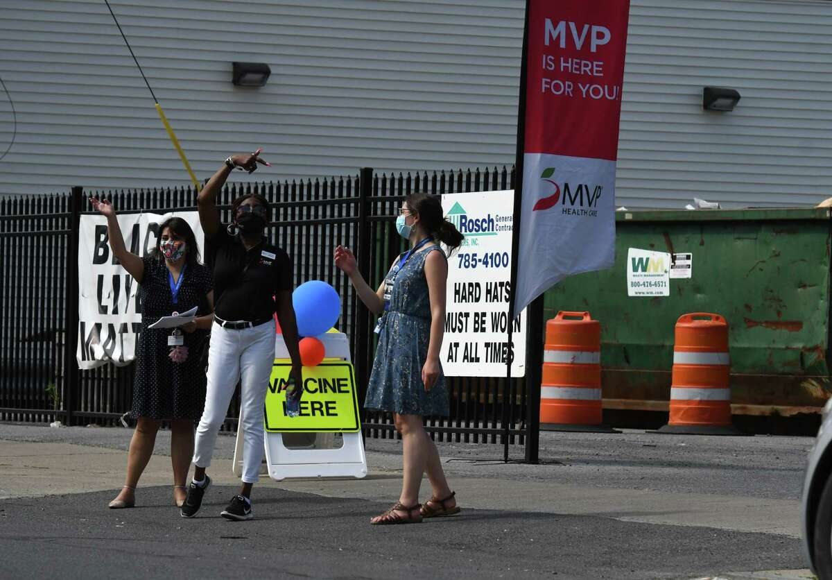 Schenectady County Health Department nurses and a representative from MVP Health Care, center, call on passersby to enter a popup mobile vaccination clinic on Thursday, May 20, 2021, at the Schenectady Inner City Mission location on Albany Street in Schenectady, N.Y. MVP Health Care, Schenectady County, and CDTA are partnering to launch a mobile COVID-19 vaccination program in Schenectady County. (Will Waldron/Times Union)