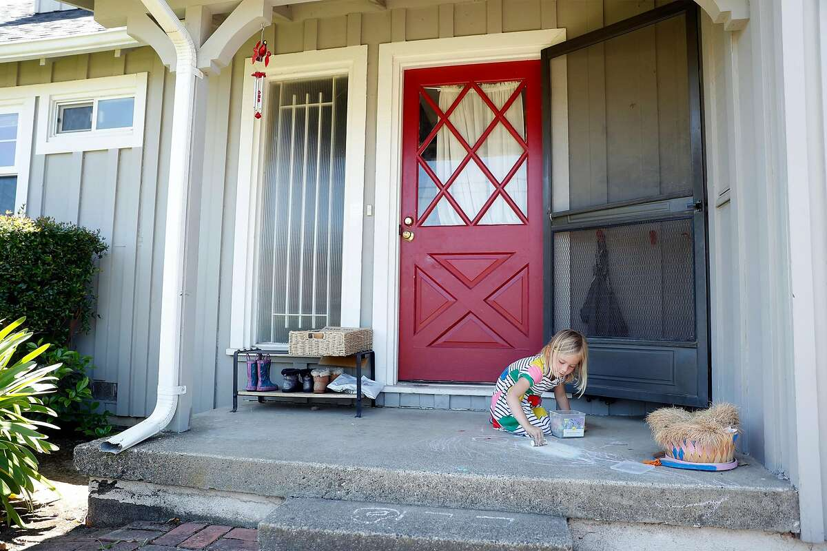 Adam and Mazy Rhuberg's daughter, Clio, 4, plays with chalk on the porch of the couple's rented home in Corte Madera. The Rhubergs pay $6,000 a month, but can't afford to buy a home in a region where the median home price just hit a record high.