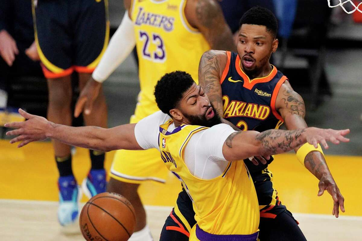 Golden State Warriors forward Kent Bazemore, right, passes the ball past Los Angeles Lakers forward Anthony Davis during the first half of an NBA basketball Western Conference Play-In game Wednesday, May 19, 2021, in Los Angeles.