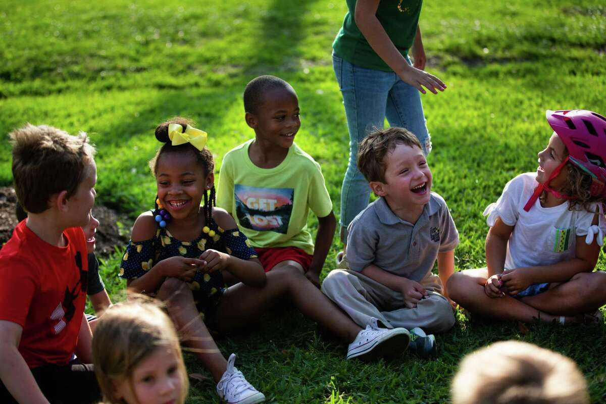 Oak Forest residents Julia Jackson, 5, Jace Jackson, 6, Mackey Bianco, 4, and Emma Mathis, 5, play duck duck goose with their neighbors, Monday, April 12, 2021, in Houston.