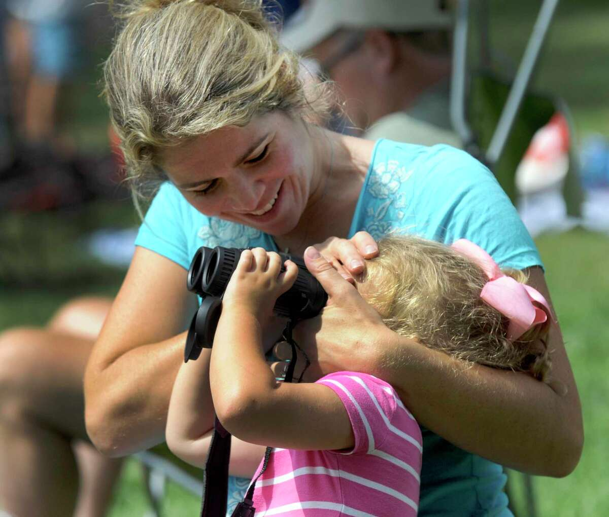 Elise Sawicki, of Wilton, helps her daughter Charlotte, 2, use SUNoculars, to safely view the solar eclipse at Ballard Park in Ridgefield Monday, August 21, 2017.