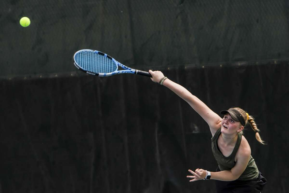 Dow's Savannah Matuszewski serves in the semi final round of the MHSAA Division 1 Region 8 Girls Tennis Championship May 20, 2021 at the Greater Midland Tennis Center in Midland. (Isaac Ritchey/for the Daily News)