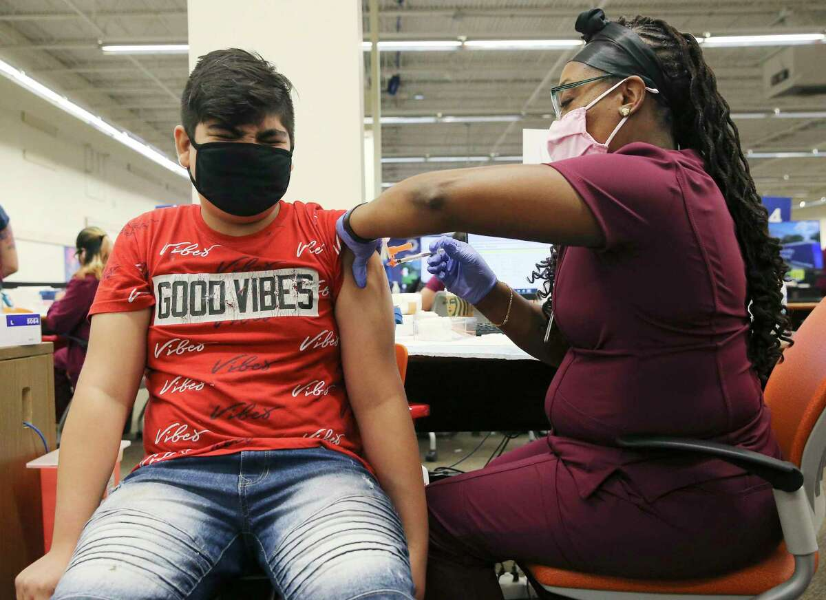 12-year-old Raymond Coronado, III winces as Medical Assistant Rockshell Johnson gives him the Pfizer Covid-19 vaccine on Thursday, May 13, 2021.