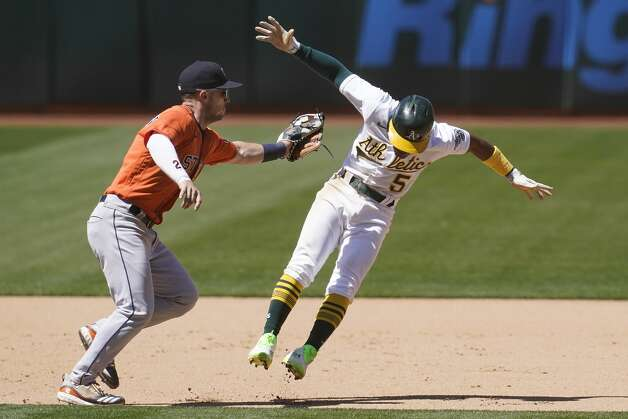 Houston Astros third baseman Alex Bregman, left, reaches to tag out Oakland Athletics' Tony Kemp during the seventh inning of a baseball game in Oakland, Calif., Thursday, May 20, 2021. (AP Photo/Jeff Chiu) Photo: Jeff Chiu/Associated Press / Copyright 2021 The Associated Press. All rights reserved