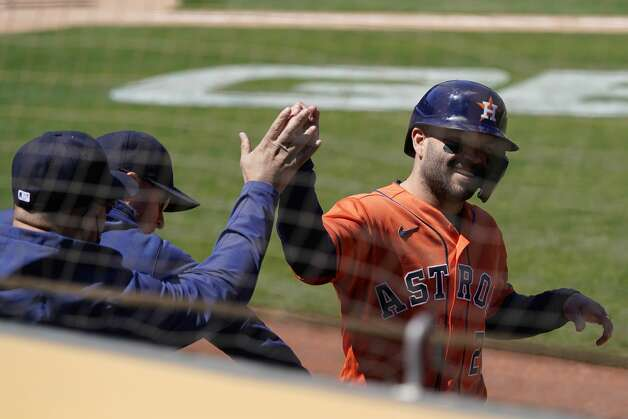 Houston Astros' Jose Altuve, right, is congratulated after scoring against the Oakland Athletics during the seventh inning of a baseball game in Oakland, Calif., Thursday, May 20, 2021. (AP Photo/Jeff Chiu) Photo: Jeff Chiu/Associated Press / Copyright 2021 The Associated Press. All rights reserved