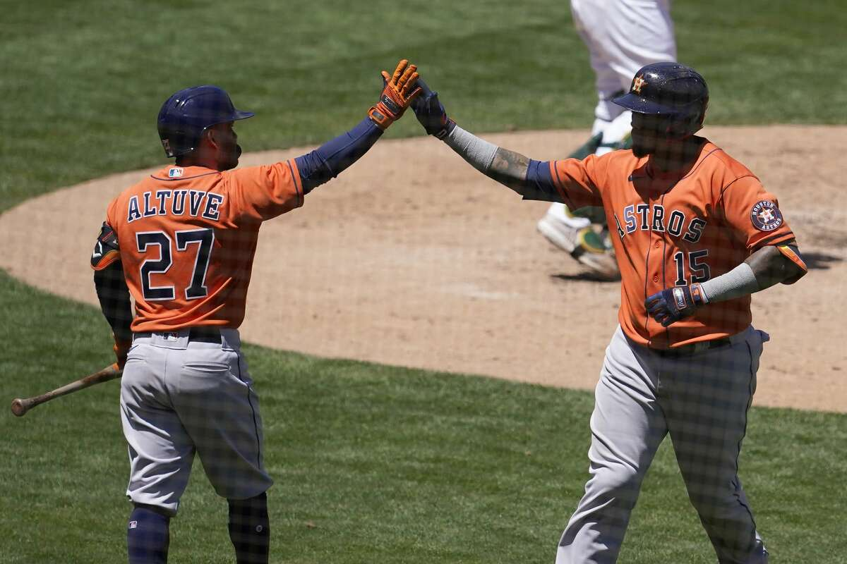 Houston Astros' Martin Maldonado, right, is congratulated by Jose Altuve after hitting a two-run home run that scored Kyle Tucker during the fourth inning of a baseball game against the Oakland Athletics in Oakland, Calif., Thursday, May 20, 2021. (AP Photo/Jeff Chiu)