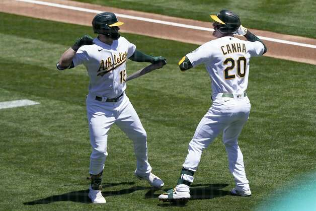 Oakland Athletics' Mark Canha (20) is congratulated by Seth Brown after hitting a home run against the Houston Astros during the first inning of a baseball game in Oakland, Calif., Thursday, May 20, 2021. (AP Photo/Jeff Chiu) Photo: Jeff Chiu/Associated Press / Copyright 2021 The Associated Press. All rights reserved