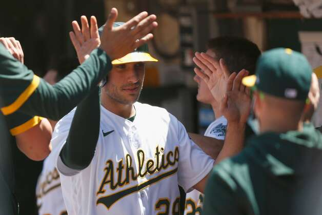 OAKLAND, CALIFORNIA - MAY 20: Matt Olson #28 of the Oakland Athletics celebrates in the dugout after scoring on a single by Jed Lowrie #8 in the bottom of the sixth inning against the Houston Astros at RingCentral Coliseum on May 20, 2021 in Oakland, California. (Photo by Lachlan Cunningham/Getty Images) Photo: Lachlan Cunningham/Getty Images / 2021 Getty Images