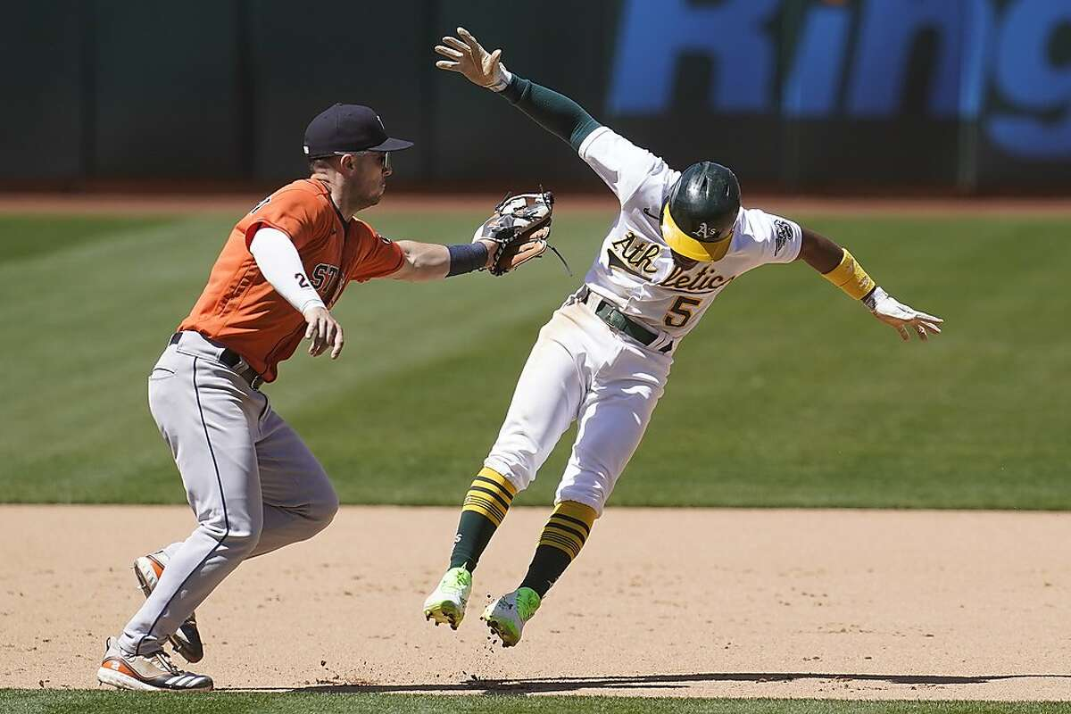 Houston Astros third baseman Alex Bregman, left, reaches to tag out Oakland Athletics' Tony Kemp during the seventh inning of a baseball game in Oakland, Calif., Thursday, May 20, 2021. (AP Photo/Jeff Chiu)