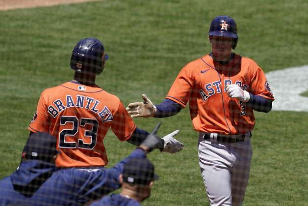 Houston Astros' Myles Straw, right, is congratulated by Michael Brantley (23) after scoring against the Oakland Athletics during the third inning of a baseball game in Oakland, Calif., Thursday, May 20, 2021. (AP Photo/Jeff Chiu) Photo: Jeff Chiu/Associated Press / Copyright 2021 The Associated Press. All rights reserved
